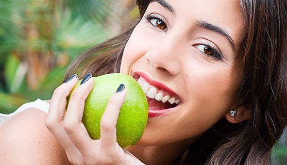 girl with beautiful teeth eating a green apple