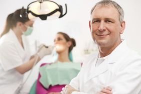 happy friendly dentist with a patient in the background and dental hygeinist