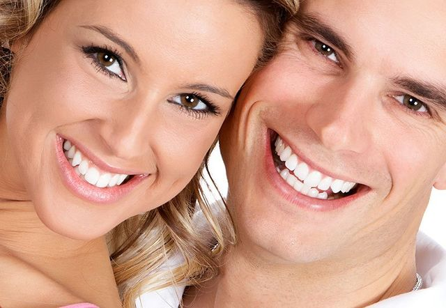 young couple smiling with beautiful teeth