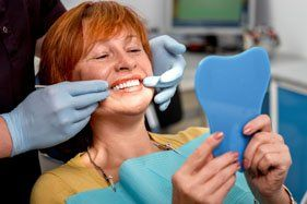 dentist looking at dental implants in a patient