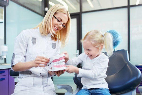 dentist showing girl teeth model