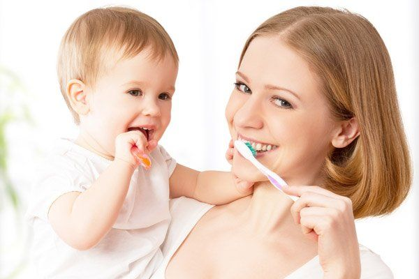 mother showing how to brush teeth to baby