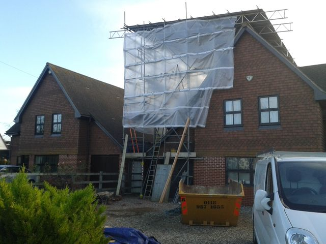 Scaffolding under protective sheeting on the front of a house