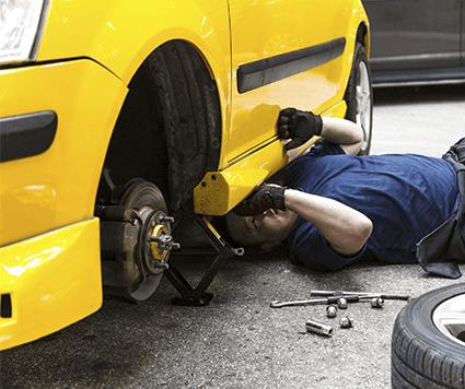 Meccanico in uniforme blu sdraiato che lavora sotto un  auto
