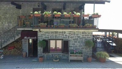 un edificio in pietra e un balcone con dei vasi di fiori