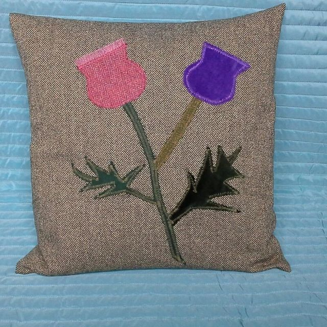 A brown cushion decorated with pink and purple applique tulips