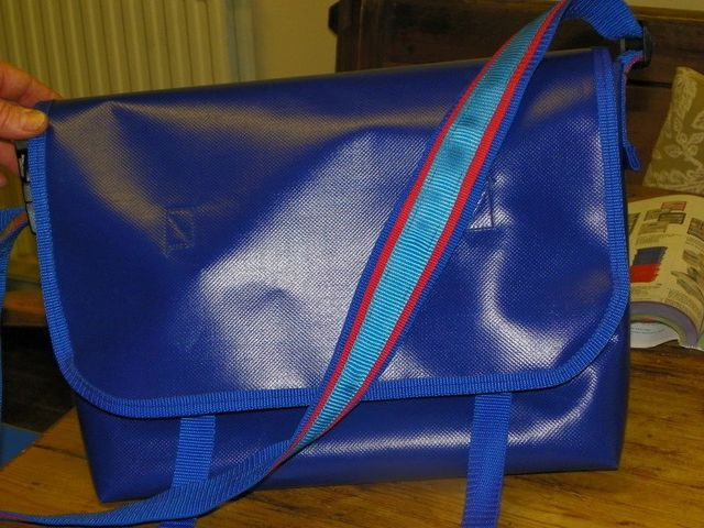 A royal blue messenger style bag with aqua and red strap