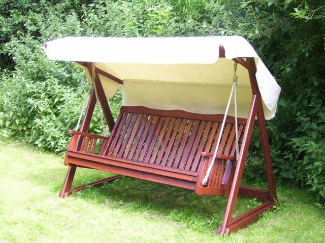 A timber garden swing seat with cream coloured canopy