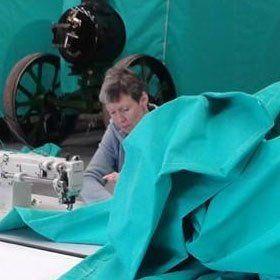 A lady stitching tarpaulin fabric on a sewing machine