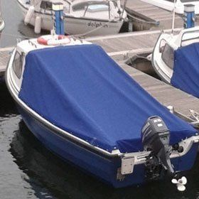 A small boat covered with blue tarpaulin, moored in a harbour