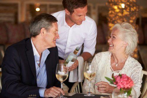 coppia di anziani al ristorante che vengono serviti dal cameriere