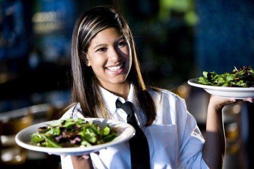 cameriera serve due piatti di insalata