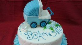 una torta a due piani con sopra un disegno di un carrozzino