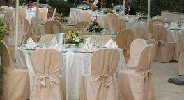 dei tavoli apparecchiati e decorati con dei fiori per una cerimonia