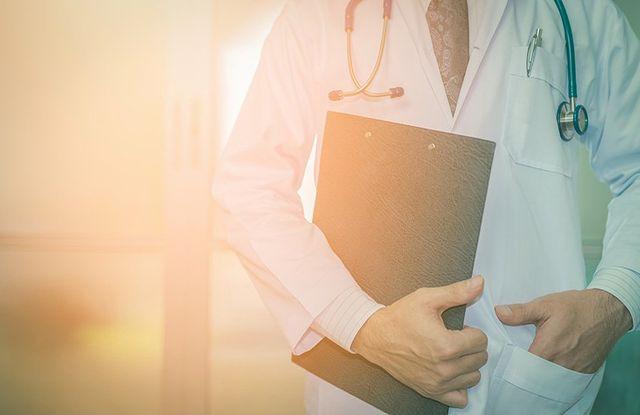 un dottore con camice bianco, stetoscopio al collo e un cartella di un paziente in mano Assemini, CA