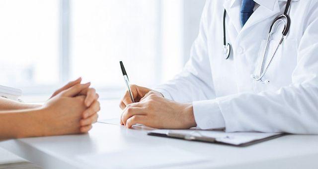 due mani di una donna di fronte a un dottore che sta prendendo appunti su un rilievo di scrittura sulla scrivania a Assemini, CA