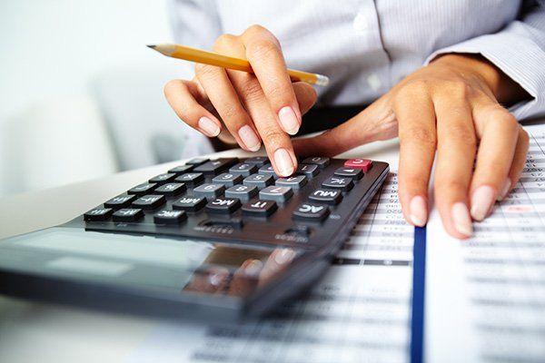 due mani con in mano una penna mentre usano una calcolatrice