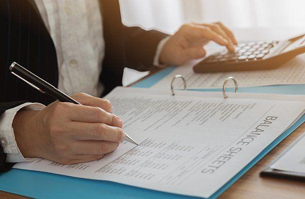 due mani, una che scrive su un foglio in un raccoglitore e l'altra che usa una calcolatrice