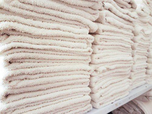 Varie pile di asciugamani bianche, lavate e stirate