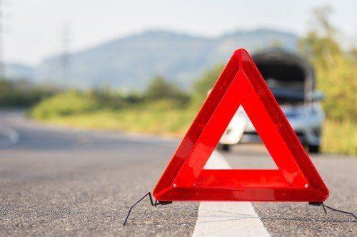 Triangolo di avvertimento e di pericolo nella strada vicino di un'automobile in avaria