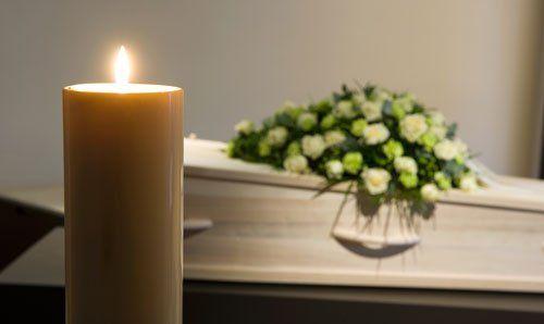 Una candela che brucia con una bara e una composizione floreale sullo sfondo in una camera mortuaria