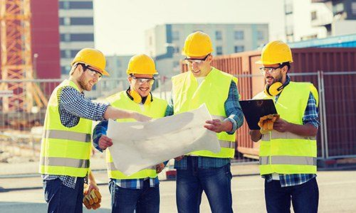 Group of smiling builders seeing blueprint