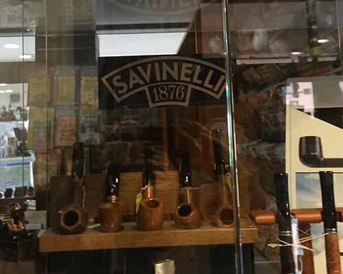 una vetrina con delle pipe con scritto Savinelli 1876