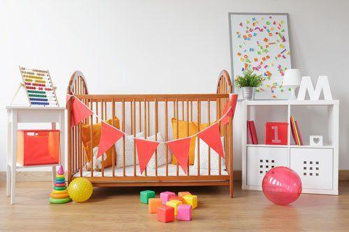 Culla in legno con cuscini di color giallo e bianco, tavolino con abaco, pavimento di parquet con un palloncino e dei giochi per bambini