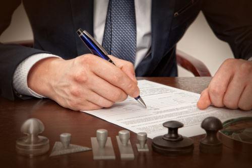 primo piano di un contratto e di una mano che scrive