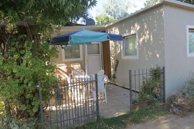 una casa da campeggio e fuori un tavolo con un ombrellone e delle sedie