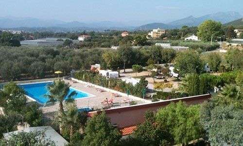 vista da lontano di una piscina e accanto dei terreni con degli alberi e delle case