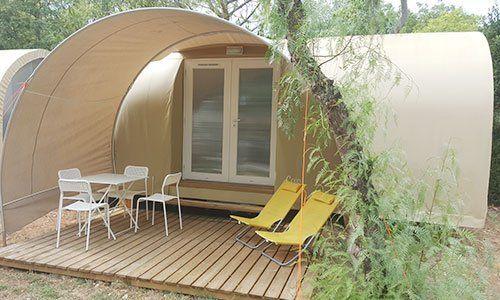 un tavolo con delle sedie, due sdraio gialle sotto una tettoia curva e vista di una porta in pvc