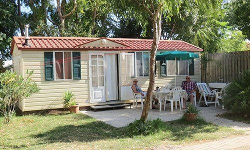 una casa da campeggio e fuori due persone sedute al tavolo sotto un ombrellone