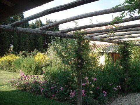 giardino fiorito con copertura di tronchi di legno
