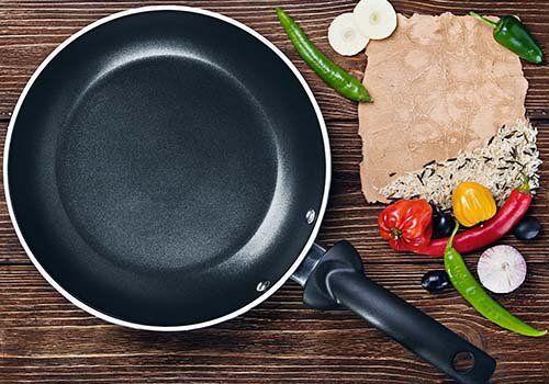 una padella con accanto degli ingredienti per cucinare