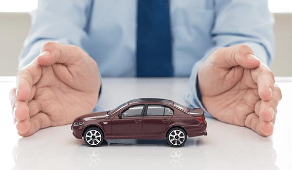 un uomo con le mani aperte con un modellino di un auto bordeaux sulla scrivania