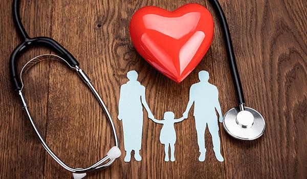 uno stetoscopio, un cuoricino rosso e l'immagine di un uomo e una donna che tengono per mano una bambina