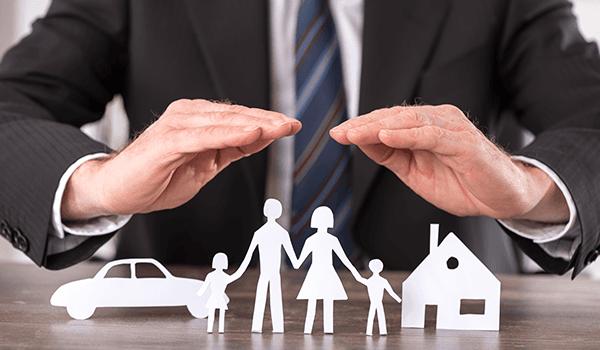 un uomo sta per coprire con le mani un modellino di un'auto, di una famiglia e di una casa