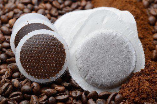 Grani di caffé ricoperti di caffè macinato e cafe in capsule o sacchetti