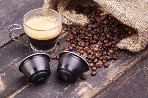 Sacco di juta aperto dove vediamo chicchi di cafe al fianco di una tazza di caffè e un paio di capsule