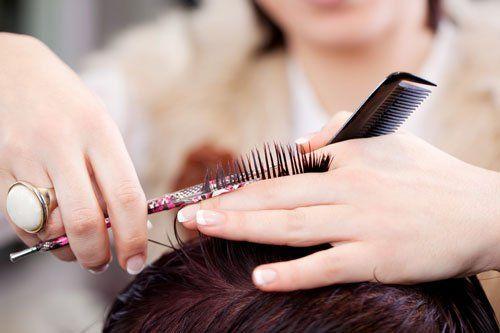 una mano che tiene dei capelli mentre li taglia con una forbice