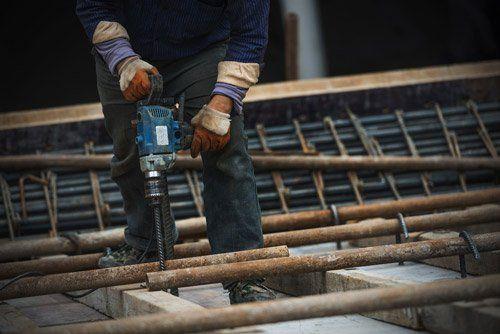 operaio mentre utilizza un trapano durante un lavoro edile