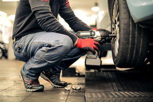 Meccanico con trapano che ripara cerchione pneumatico