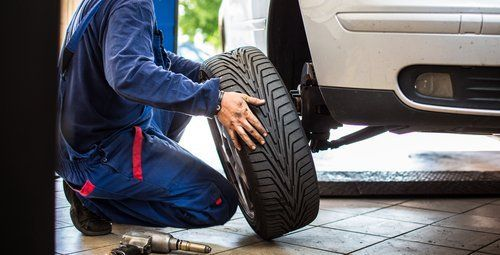 Meccanico che sostituisce pneumatico auto
