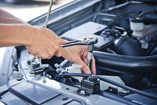 Meccanico che riapra motore auto con chiave inglese
