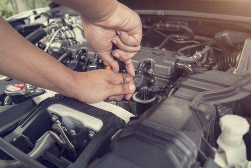 Meccanico che ripara motore auto con cacciavite
