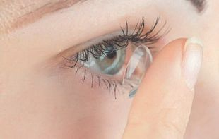 a woman putting a contact lense in