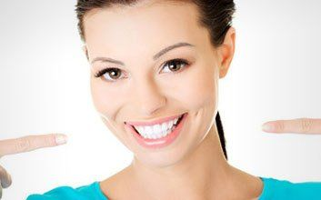 A smiling lady pointing at her own healthy white teeth