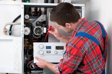 addetto con cacciavite mentre sistema un collegamento di un impianto centralizzato