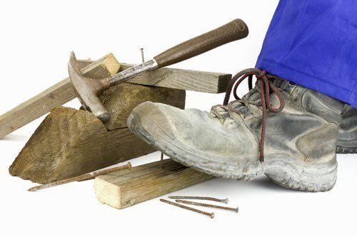 una scarpa antinfortunistica  che calpesta dei pezzi di legno e un martello